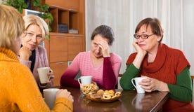 Amis féminins supérieurs tristes buvant du thé Images stock
