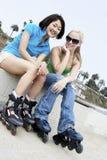 Amis féminins sur des patins de rouleau Image stock