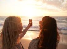 Amis féminins sur le coucher du soleil de photographie de plage Photographie stock