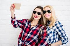 Amis féminins sur le fond blanc de mur Images stock
