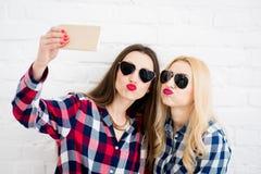 Amis féminins sur le fond blanc de mur Image libre de droits