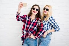 Amis féminins sur le fond blanc de mur Photos stock