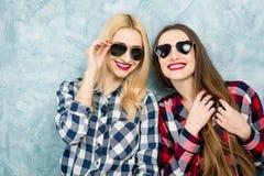 Amis féminins sur le fond bleu de mur Photographie stock