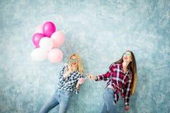 Amis féminins sur le fond bleu de mur Photographie stock libre de droits