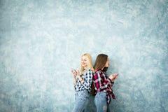 Amis féminins sur le fond bleu de mur Images stock