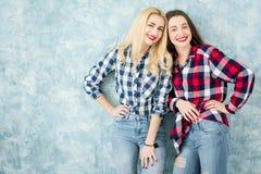 Amis féminins sur le fond bleu de mur Images libres de droits