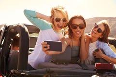 Amis féminins sur le voyage par la route dans la voiture convertible prenant Selfie Images libres de droits