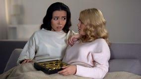 Amis féminins tenant des bonbons au chocolat combattant avec désir de consommation, hormones photos libres de droits