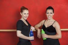 Amis féminins tenant des bouteilles d'eau dans le studio de ballet Photo stock