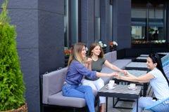 Amis féminins tenant des mains au café et buvant du café Image libre de droits