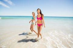 Amis féminins tenant des mains sur la plage Images stock