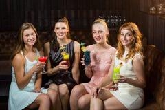 Amis féminins tenant des verres de cocktail dans la barre Image libre de droits
