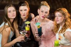 Amis féminins tenant des verres de cocktail dans la barre Photos stock