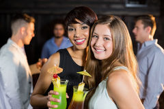 Amis féminins tenant des verres de cocktail dans la barre Images stock