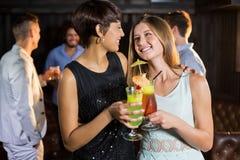 Amis féminins tenant le verre du cocktail dans la barre Photos stock