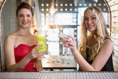 Amis féminins tenant le verre du cocktail dans la barre Images stock