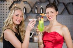 Amis féminins tenant le verre du cocktail dans la barre Image libre de droits