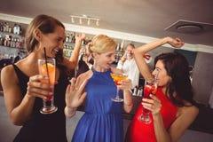 Amis féminins tenant le verre du cocktail tout en dansant Photographie stock libre de droits