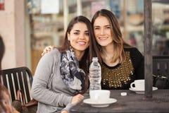 Amis féminins traînant à un café Photo stock