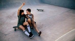 Amis féminins traînant au parc de patin Photos stock