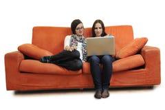 Amis féminins travaillant sur l'ordinateur portable à la maison Photographie stock libre de droits