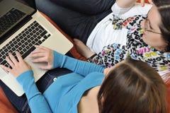 Amis féminins travaillant sur l'ordinateur portable à la maison Image libre de droits