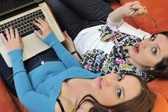 Amis féminins travaillant sur l'ordinateur portable à la maison Images stock