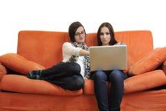Amis féminins travaillant sur l'ordinateur portable à la maison Photo stock