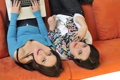 Amis féminins travaillant sur l'ordinateur portable à la maison Photos stock