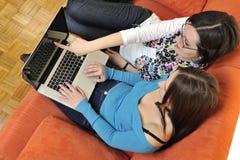 Amis féminins travaillant sur l'ordinateur portable à la maison Photographie stock