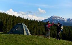 Amis féminins trimardant ensemble dans les montagnes photographie stock