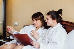 Amis féminins utilisant les peignoirs blancs détendant dans un hôtel Photos stock