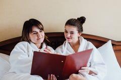 Amis féminins utilisant les peignoirs blancs détendant dans un hôtel Photographie stock libre de droits