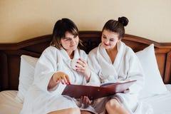 Amis féminins utilisant les peignoirs blancs détendant dans un hôtel Images libres de droits