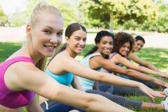Amis faisant étirant l'exercice au parc Image libre de droits
