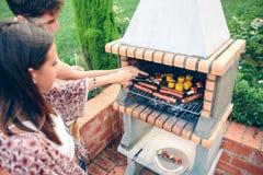 Amis faisant cuire dans le barbecue sur la partie d'été Image stock