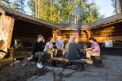 Amis faisant cuire la nourriture par le hangar dans la forêt Image libre de droits