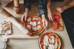 Amis faisant cuire la pizza faite maison ensemble, vue supérieure Photo libre de droits