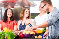 Amis faisant cuire les pâtes et la viande dans la cuisine domestique Image libre de droits