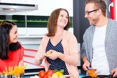 Amis faisant cuire les pâtes et la viande dans la cuisine domestique Photographie stock libre de droits