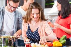 Amis faisant cuire les pâtes et la viande dans la cuisine domestique Photo libre de droits