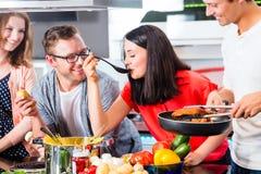 Amis faisant cuire les pâtes et la viande dans la cuisine domestique Photos stock