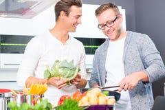 Amis faisant cuire les vegies et la viande dans la cuisine domestique Images stock