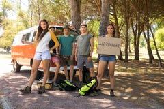 Amis faisant de l'auto-stop tout en se tenant prêt le camping-car Image libre de droits