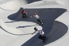 Amis faisant de la planche à roulettes en parc Image libre de droits