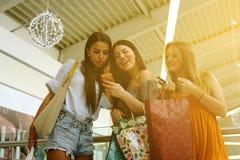 Amis faisant des emplettes ensemble et à l'aide du téléphone intelligent Images libres de droits