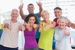 Amis faisant des gestes des pouces dans le centre de fitness Image stock