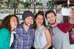 Amis faisant des visages tout en parlant le selfie dans le restaurant Photos libres de droits
