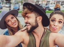 Amis faisant des visages tout en prenant le selfie Photos stock