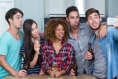 Amis faisant des visages tout en prenant le selfie dans la cuisine Photographie stock